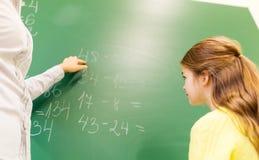 Scolara ed insegnante con il compito sul bordo di gesso Immagine Stock