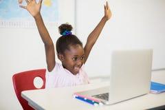 Scolara emozionante con il computer portatile in aula Fotografia Stock