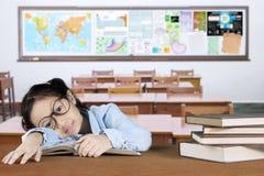 Scolara esaurita con i libri sulla tavola Fotografie Stock Libere da Diritti