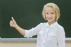 Scolara felice che mostra pollice su in un'aula vicino alla lavagna verde Il bambino gradisce imparare fotografie stock