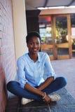 Scolara felice che si siede accanto al muro di mattoni nella città universitaria della scuola Immagini Stock