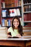 Scolara felice che si siede con la pila di libri dentro Fotografia Stock