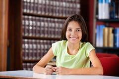 Scolara felice che si siede nella biblioteca Immagine Stock Libera da Diritti