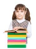 Scolara felice con i libri della pila Isolato su priorità bassa bianca Immagine Stock