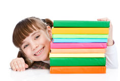Scolara felice con i libri della pila Isolato su priorità bassa bianca Fotografia Stock