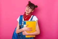Scolara felice con la cartella della carta isolata su fondo ottimistico Ragazza sorridente che è felice di ritornare scuola dopo  fotografie stock libere da diritti