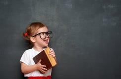 Scolara felice della ragazza con il libro dalla lavagna Fotografie Stock