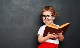 Scolara felice della ragazza con il libro dalla lavagna Immagini Stock Libere da Diritti