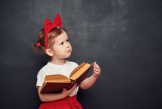 Scolara felice divertente della ragazza con il libro dalla lavagna Immagine Stock Libera da Diritti