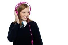 Scolara graziosa che gode della musica Immagine Stock