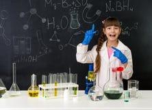 Scolara nel laboratorio di chimica che indica alla formula sulla lavagna Fotografia Stock Libera da Diritti