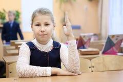 Scolara russa in uniforme che si siede allo scrittorio in stanza di classe e mano in aumento su La Russia Fotografie Stock Libere da Diritti