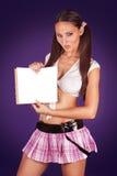 Scolara sexy che tiene un libro aperto che mostra un documento in bianco Fotografia Stock