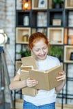 Scolara sorridente che legge un libro Il concetto dello stile di vita, 'chi' Immagini Stock