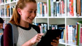 Scolara sorridente che utilizza compressa digitale nella biblioteca archivi video