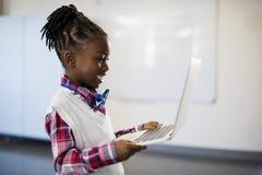 Scolara sorridente che utilizza computer portatile nell'aula Fotografie Stock Libere da Diritti