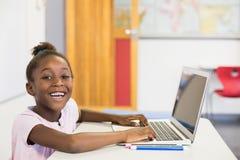 Scolara sorridente che utilizza computer portatile nell'aula Fotografia Stock