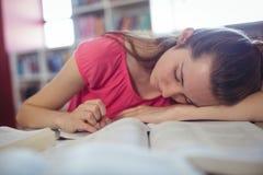 Scolara stanca che dorme mentre studiando nella biblioteca Fotografia Stock