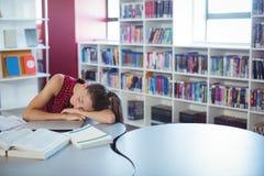 Scolara stanca che dorme mentre studiando nella biblioteca Fotografie Stock Libere da Diritti