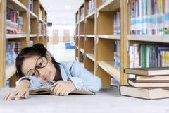 Scolara sveglia che dorme nella biblioteca Fotografia Stock Libera da Diritti