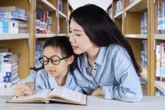 Scolara sveglia che legge un libro con il suo insegnante Fotografia Stock