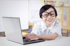Scolara sveglia con il computer portatile nella classe Immagini Stock