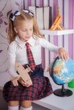 Scolara sveglia con il globo e l'aeroplano che si siedono sulla tavola Fotografia Stock Libera da Diritti