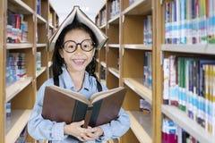Scolara sveglia con un libro sopra la sua testa Fotografie Stock