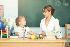 Scolara sveglia ed il suo insegnante in un'aula Immagini Stock