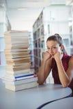 Scolara triste che esamina pila di libri in biblioteca Fotografia Stock