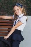 Scolara in uniforme che aspetta il bus alla scuola Immagine Stock