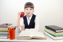 Scolara in uniforme con il libro e la mela rossa Fotografie Stock Libere da Diritti