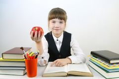 Scolara in uniforme con il libro e la mela rossa Fotografie Stock