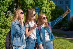 Scolare delle ragazze di estate in parco Prende le immagini se stesso sul telefono Posa sorridente felice sulla macchina fotograf Fotografia Stock