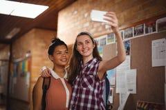 Scolare felici che prendono selfie sul telefono cellulare in corridoio Fotografia Stock