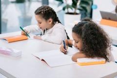 Scolare multietniche che scrivono e che studiano allo scrittorio nella classe Fotografia Stock