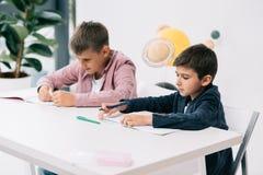 Scolari caucasici che studiano insieme allo scrittorio in aula Immagini Stock Libere da Diritti