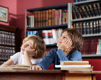 Scolari che distolgono lo sguardo mentre sedendosi nella biblioteca Immagine Stock Libera da Diritti