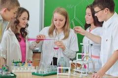 Scolari che fanno esperimento nella classe di scienza Immagini Stock