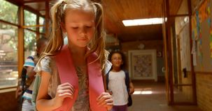 Scolari che opprimono una ragazza triste in corridoio di scuola elementare 4k archivi video