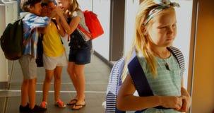 Scolari che opprimono una ragazza triste nel corridoio di scuola elementare 4k stock footage