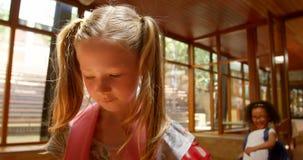 Scolari che opprimono una ragazza triste nel corridoio di scuola elementare 4k video d archivio