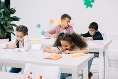 Scolari che scrivono in quaderni e che studiano insieme nell'aula Fotografia Stock
