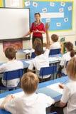 Scolari che studiano nell'aula con l'insegnante Immagini Stock