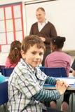 Scolari che studiano nell'aula con l'insegnante Fotografia Stock