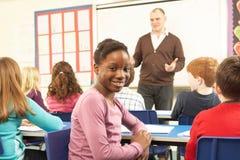 Scolari che studiano nell'aula con l'insegnante Fotografie Stock