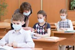 Scolari con le maschere di protezione contro il virus di influenza alla lezione immagine stock