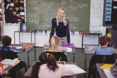 Scolari d'aiuto dell'insegnante con il loro compito in aula Immagine Stock Libera da Diritti