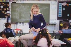 Scolari d'aiuto dell'insegnante con il loro compito in aula Immagini Stock Libere da Diritti