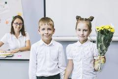 Scolari dei bei bambini con i fiori per gli insegnanti Fotografie Stock
